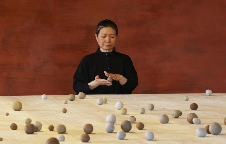 L'artiste Kimssoja, à table, en train de rouler de petites boules d'argiles. Installation « Archive of Mind » (2017).