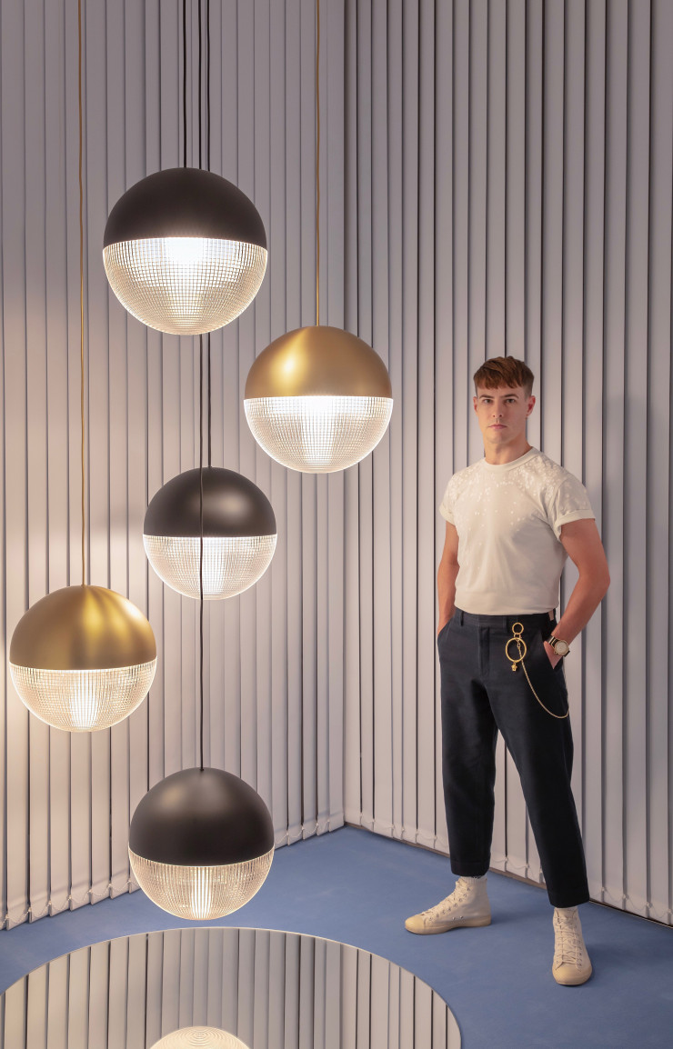 Lee Broom au côté de ses lampes Lens Flair.