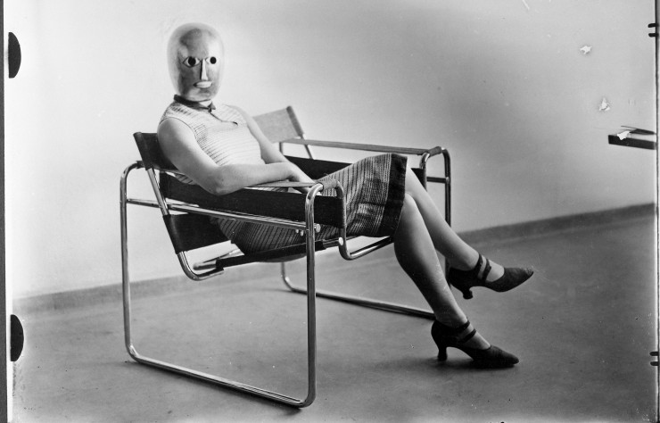 Woman Wearing a Theatrical Mask by Oskar Schlemmer and Seated on Marcel Breuer's Tubular-Steel Chair (1926).